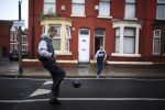 Youths play football in the street in Liverpool, England