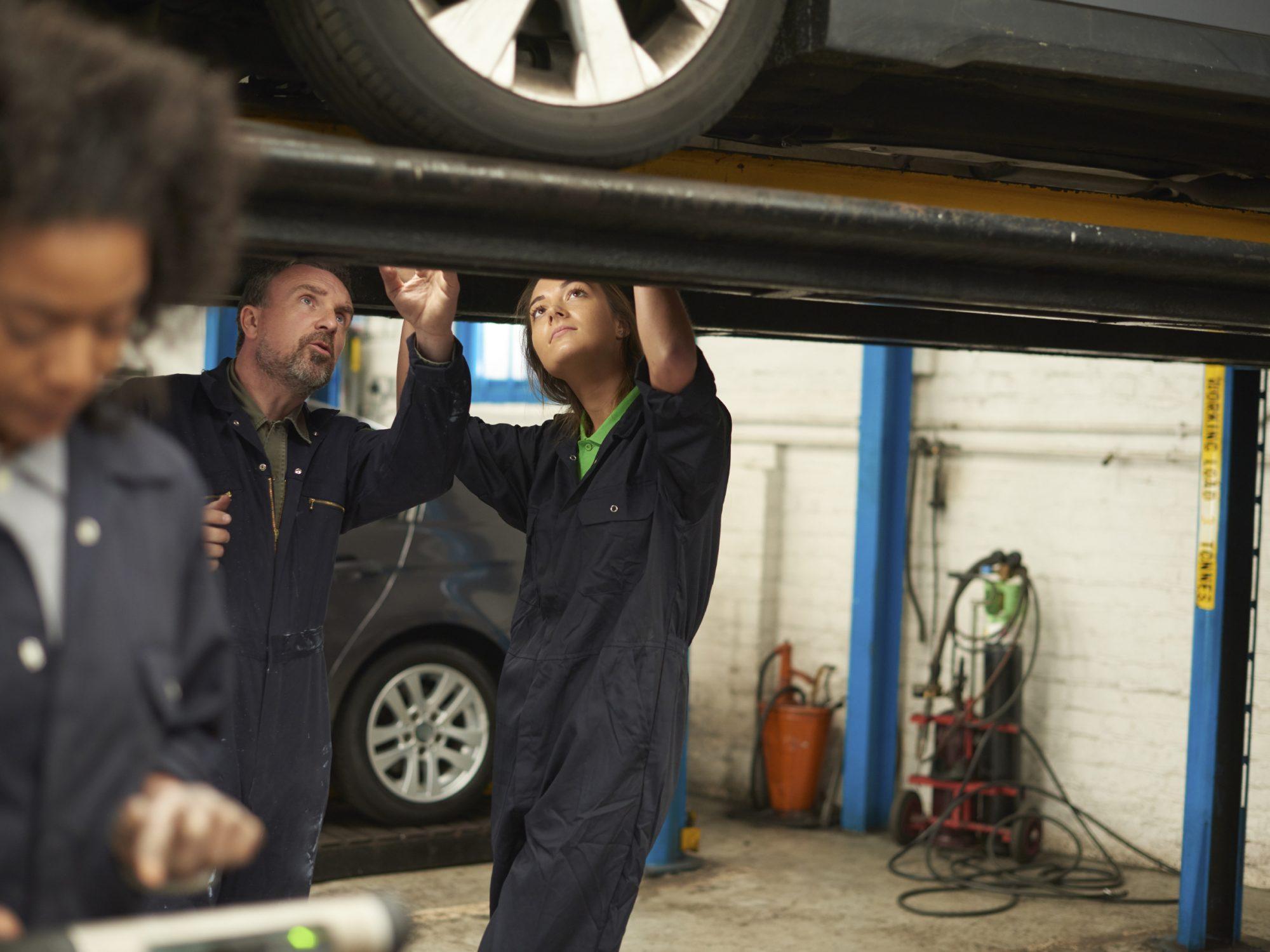 Senior mechanic teaching an apprentice